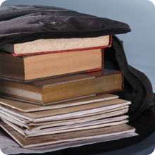 stack of books and notebooks in open backpack